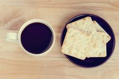 Tasse Kaffee auf Holztisch mit Cracker in der Platte: Draufsicht Stockfotografie