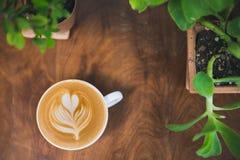 Tasse Kaffee auf Holztisch, Pflänzchen, Grün, Hintergrund Lizenzfreie Stockfotos