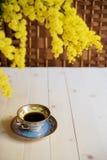 Tasse Kaffee auf Holztisch und Mimose Lizenzfreies Stockfoto