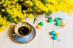 Tasse Kaffee auf Holztisch und Mimose Lizenzfreie Stockbilder