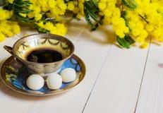 Tasse Kaffee auf Holztisch und Mimose Stockbild