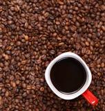 Tasse Kaffee auf Kaffeebohnehintergrund Lizenzfreie Stockfotos