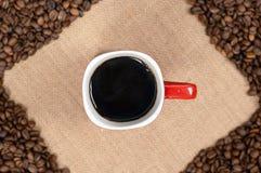 Tasse Kaffee auf Kaffeebohnehintergrund Stockbilder