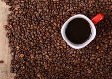 Tasse Kaffee auf Kaffeebohnehintergrund Stockfoto