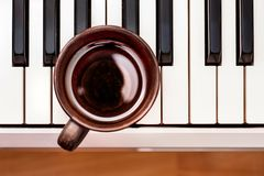Tasse Kaffee auf Klavierschlüsseln, tonisches Getränk, zum von Ermüdung zu entlasten, lizenzfreie stockfotos