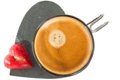 Tasse Kaffee auf Steinherzformfußball, mit kleinem rotem chocol Stockbild