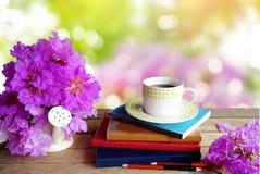 Tasse Kaffee, Bücher, Bleistifte und purpurroter Frühling blühen über Naturhintergrund Stockfoto