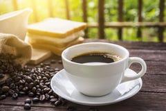 Tasse Kaffee-Bohnen auf dem Tisch mit hellem Sonnenlicht an der Dämmerungs-/Konzeptweinlese Stockfotos