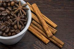 Tasse Kaffee-Bohnen mit Zimt lizenzfreie stockfotos