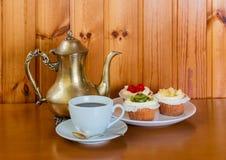 Tasse Kaffee, Bonbon backt mit Früchten und Kaffeetopf zusammen Lizenzfreies Stockbild