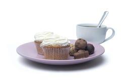 Tasse Kaffee, Bonbons und Kuchen auf der Platte Lizenzfreie Stockfotos
