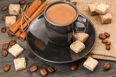 Tasse Kaffee, brauner Zucker, Bohnen und Zimt auf einem hölzernen und Leinwandhintergrund Lizenzfreies Stockfoto