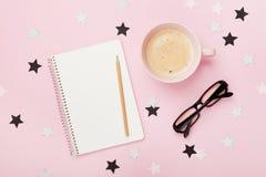 Tasse Kaffee, Brillen, Bleistift und sauberes Notizbuch auf rosa Tischplatteansicht flache Lageart Frau Bloggerarbeitsschreibtisc Stockbilder