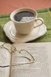 Tasse Kaffee, Buch im Hintergrund Lizenzfreie Stockfotos