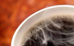 Tasse Kaffee-Dämpfen heiß mit orange Hintergrund Lizenzfreies Stockfoto