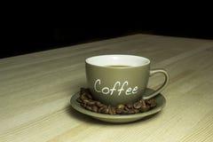 Tasse Kaffee, der auf einem Holztisch steht Lizenzfreie Stockfotos
