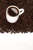 Tasse Kaffee, der auf Kaffeebohnen steht Lizenzfreie Stockbilder