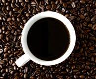 Tasse Kaffee, der auf Kaffeebohnen steht stockfotos