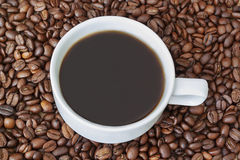 Tasse Kaffee, der durch Bohnen umgibt Lizenzfreie Stockfotos