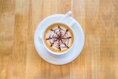 Tasse Kaffee in der Mitte auf hölzernem Hintergrund lizenzfreies stockfoto