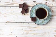Tasse Kaffee, dunkle Schokolade auf Holztisch stockfoto