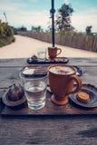 Tasse Kaffee, ein Glas Wasser und Plätzchen auf dem Holztisch Stockbilder