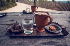 Tasse Kaffee, ein Glas Wasser und Plätzchen auf dem Holztisch Lizenzfreie Stockfotografie