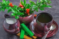 Tasse Kaffee, ein Krug Milch-, Schokoladen- und Granatapfelbaumaste mit Blumen auf einem dunklen Hintergrund Lizenzfreie Stockbilder