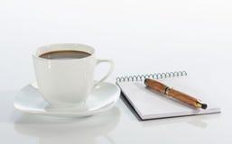 Tasse Kaffee, Feder und Notizbuch stockbild