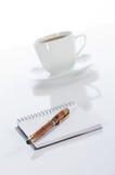 Tasse Kaffee, Feder und Notizbuch Stockfotografie