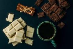 Tasse Kaffee, gebrochene weiße und schwarze Schokoriegel und Stapel Zimt auf schwarzer Tabelle, Draufsicht Lizenzfreie Stockfotos