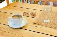 Tasse Kaffee, Gläser, Wasser auf Tabelle lizenzfreies stockbild