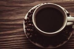 Tasse Kaffee, Kaffeebohnen auf Untertasse auf hölzernem Hintergrund lizenzfreie stockfotos