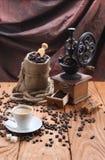 Tasse Kaffee, Kaffeemühle, Kaffeebohnen in einem Sack Lizenzfreies Stockbild