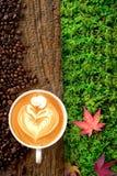 Tasse Kaffee Latte und Kaffeebohne fallen auf alte Barke mit drei Stockfotografie