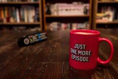 Tasse Kaffee mit Aufschrift gerade eine weitere Episode und Fernsehdirektübertragungsprüfer Stockfotografie