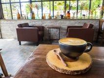 Tasse Kaffee mit Baummuster in der schwarzen Schale Lizenzfreies Stockbild