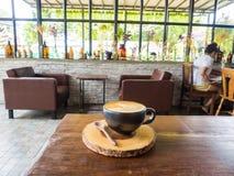 Tasse Kaffee mit Baummuster in der schwarzen Schale Lizenzfreie Stockfotos