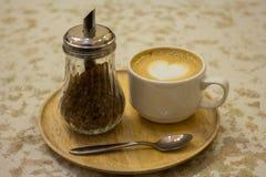 Tasse Kaffee mit Blattmuster in einer weißen Schale Stockfoto
