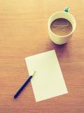 Tasse Kaffee mit Bleistift- und Papieranmerkung Stockfoto