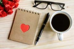 Tasse Kaffee mit Blume und Notizblock auf Holztisch Lizenzfreies Stockfoto