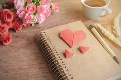 Tasse Kaffee mit Blume und rotes Herz formen Papier und Notizblock Stockbild