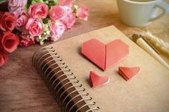 Tasse Kaffee mit Blume und rotes Herz formen Papier und Notizblock Stockbilder