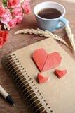 Tasse Kaffee mit Blume und rotes Herz formen Papier und Notizblock Lizenzfreie Stockfotos