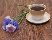Tasse Kaffee mit Blumenkornblumen Stockfotografie