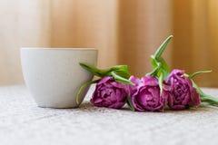 Tasse Kaffee mit Blumenstrauß von violetten Tulpen auf einem beige backgroun Lizenzfreie Stockfotos