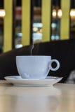Tasse Kaffee mit Bohnen auf Tabelle im Café Lizenzfreie Stockfotografie