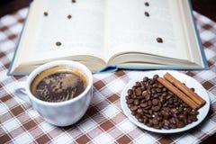 Tasse Kaffee mit Bohnen und Buch auf der Tischdeckennahaufnahme Stockbild