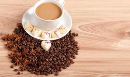 Tasse Kaffee mit Bohnen und weißer Schokoladeninnersüßigkeit über hölzernem Hintergrund Lizenzfreie Stockfotos