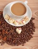 Tasse Kaffee mit Bohnen und weißer Schokoladeninnersüßigkeit über hölzernem Hintergrund Lizenzfreies Stockbild